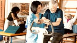 Image: A physiotherapist is helping an older man to use an ergometer; Copyright: panthermedia.net/jovannig
