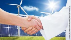 Image: Shaking hands of two people, one of them wearing a doctor's coat, in front of wind turbines and solar panels in the sun; Copyright: PantherMedia/Wavebreakmedia (YAYMicro)
