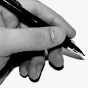 Photo: A hand holding a pen in order to write