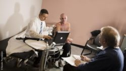 Image: Two physicians are talking to a wheelchair user; Copyright: Kessler Foundation