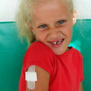 Foto: Little girl with vaccination plaster makes a grimace