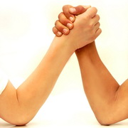 Photo: two persons testing their strength by arm wrestling