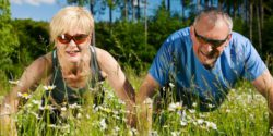Photo: Two senior citizens do pushups at a forest glade; Copyright: panthermedia.net/Arne Trautmann