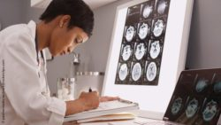 Image: Young female radiologist is looking at pictures of the head and takes some notes; Copyright: panthermedia.net/mark@rocketclips.com