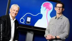 Image: two men in front of a screen presenting the electrodes on the head to target epilepsy; Copyright: Bart van Overbeeke