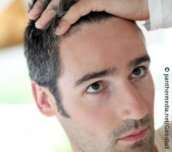 Image: A man is looking into the mirror at his not-yet-grey hair; Copyright: panthermedia.net/Goodluz