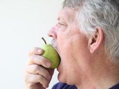 Photo: Older man eating a pear