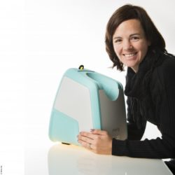 Image: Woman puts her arms around the retina scanner and looks smilingly to the side into the camera; Copyright: Mimo AG