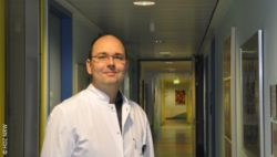 Photo: Smiling young physician with glasses and a white coat in the hallway of a hospital; Copyright: HDZ NRW