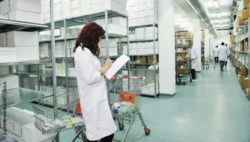 Image: Hospital warehouse in which a woman with a coat, clipboard and shopping carts is standing; Copyright: panthermedia.net/.shock