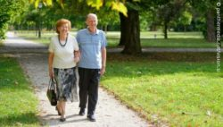 Image: Two older people walking through a park, smiling; Copyright: panthermedia.net/vision.si