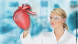 Image: Woman in white coat looks at hologram with a heart; Copyright: panthermedia.net / Wavebreakmedia ltd