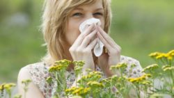 Image: woman who cleans her nose among flowers; Copyright: Fotolia