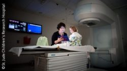 Photo: Female physician and a girl at a radiation therapy treatment room