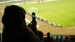 Photo: Spectator at a stadium takes a photo with his mobile phone; Copyright:panthermedia.net/ shufu