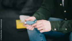 Image: A person is sitting on a sofa and holds a small inhaler in his hands; Copyright: PantherMedia/Andrew Lozovyi