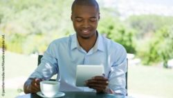 Image: A young man is drinking a cup of coffee while reading from a tablet computer; Copyright: panthermedia.net/Waverbreakmedia Ltd.