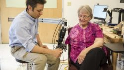 Image: Man touching prosthetic arm next to an older woman; Copyright: UPMC