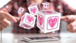 Image: Colorful cubes with heart symbols are floating over a smartphone; Copyright: panthermedia.net/thodonal