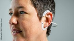 Image: A woman with a round wearable device around her ear; Copyright: Fraunhofer IDMT/Hannes Kalter