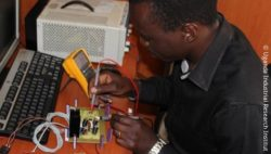 Image: electrical engineer tests a circuit used to supply power to the ECGF-IS gravity-feed infusion set; Copyright: Uganda Industrial Research Institute