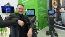 Image: Stefan Küper sitting on a training device at the eGym booth at MEDICA 2019; Copyright: beta-web/Koller