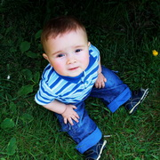 Photo: Little boy sitting in the grass looking up