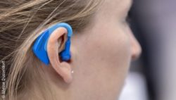 Image: Trade fair visitor with a blue plug in her ear; Copyright: Messe Düsseldorf