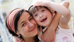 Image: smiling woman and littler girl with down syndrome; Copyright: panthermedia.net/DenysKuvaiev