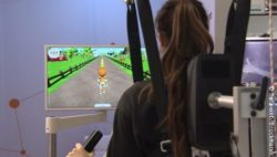 Photo: A woman is using an exoskeleton of Hocoma and plays a video game; Copyright: beta-web/Brockmann