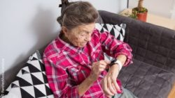 Image: An old woman is using a smartwatch; Copyright: PantherMedia/veloliza