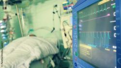 Image: A monitor at an intensive care unit, next to it a patient in a bed; Copyright: PantherMedia/sudok1