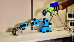 Image: robotic hand connected with a human hand; Copyright: Texas A&M University College of Engineering