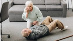 Image: An older man lies on the ground and presses a hand to his head, his wife kneels next to him and calls an ambulance; Copyright: PantherMedia/AndrewLozovyi
