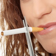 Photo: Woman cuts through a cigarette she has in her mouth