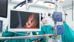 Image: A monitor and different displays in the OR, behind this the OR team; Copyright: panthermedia.net/chanawit