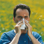 Photo: Man surrounded by grass blowing his nose
