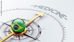 Image: A ball that shows the Brazilian flag lies on top of a compass needle that points towrads the word