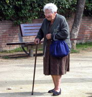 Photo: Old woman with a walking stick walks along the street