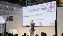 Image: Speaker on the stage of the MEDICA App COMPETITION; Copyright: Messe Düsseldorf