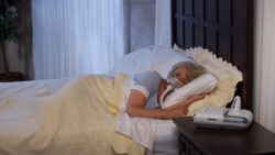 Picture: Woman sleeping sideways in bed with a breathing mask; Copyright: Philips GmbH