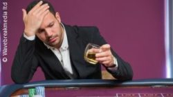 Image: Man sitting at a gambling table, with a drink in his hand, looking sad; Copyright: panthermedia.net/Wavebreakmedia ltd