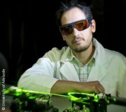 Image: Researcher with protective glasses sits next to a laboratory device emitting a beam of green light; Copyright: University of Adelaide