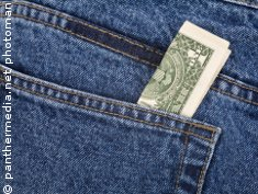 Photo: A dollar note showing from a jeans pocket