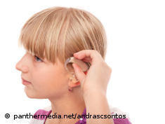 Photo: Girl puts a hearing aid into her ear