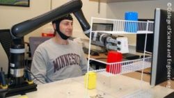 Photo: Man moving a robotic arm with his mind; Copyright: College of Science and Engineering