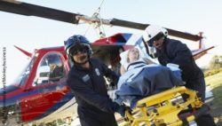 Photo: Paramedics and patient in front of rescue chopper; Copyright: panthermedia.net/monkeybusiness