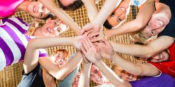 Image: A team of young people is standing together in a circle, putting their hands together; Copyright: panthermedia.net/Kzenon