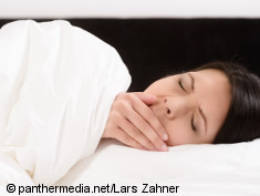 Photo: woman yawning whil lying in bed