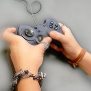 Photo: Hand holding a joystick, pushing a button